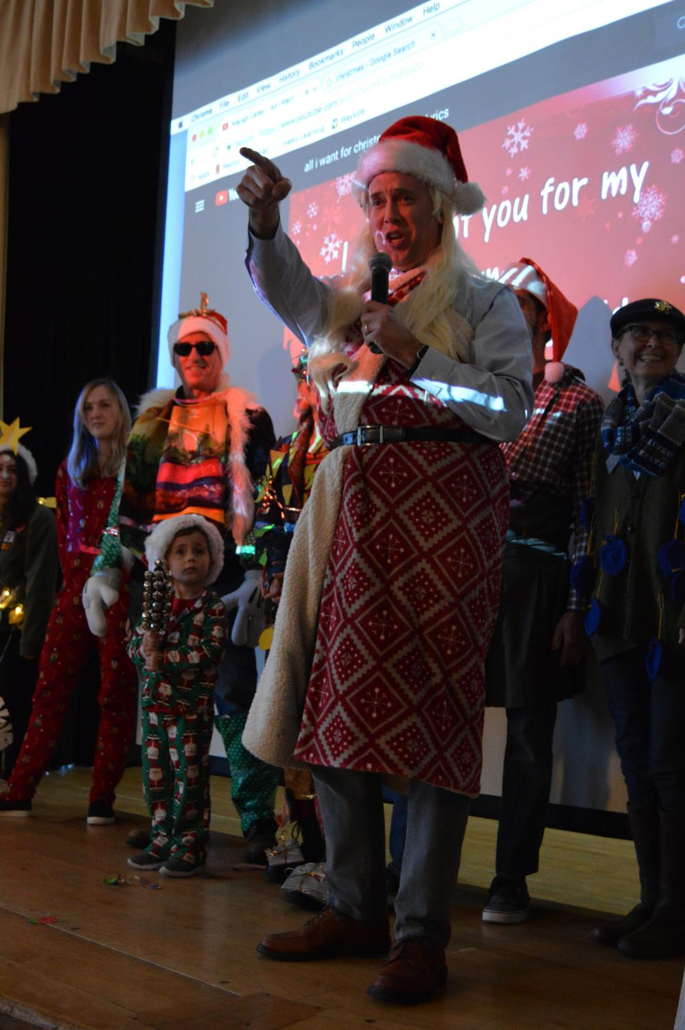 History teacher Michael Stafford lip-syncs during the advisor costume contest. Stafford, along with numerous other advisors, were dressed up by their advisees as Christmas-related figures as a part of the four-hour holiday celebration.