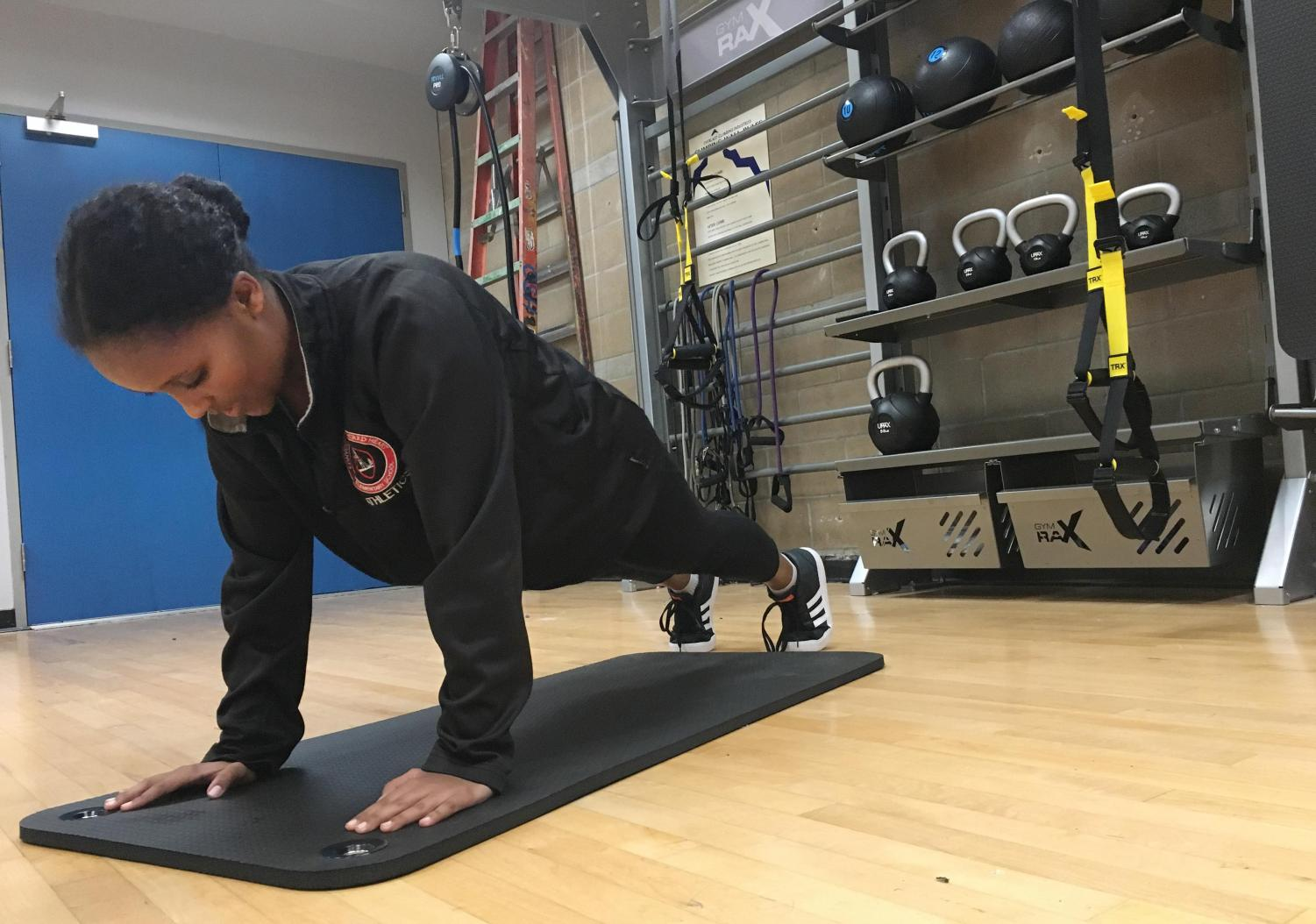 Senior Edna Tesfaye holds a plank in the newly redone multi-purpose room. The conditioning session alternates between the two reconstructed training rooms.