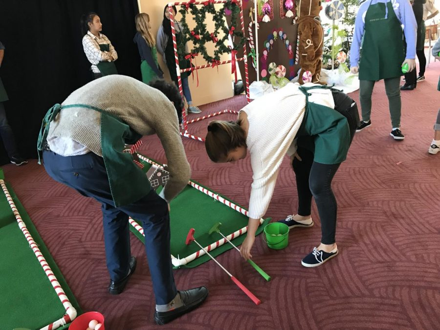 Sophomores Sofia Telfer and Henry Sears set up a game of miniature golf prior to the arrival of children at 'Deck the Hall'. 'Deck the Hall' is an annual event hosted by Davies Symphony Hall, which includes games, photos with Santa and a concert.