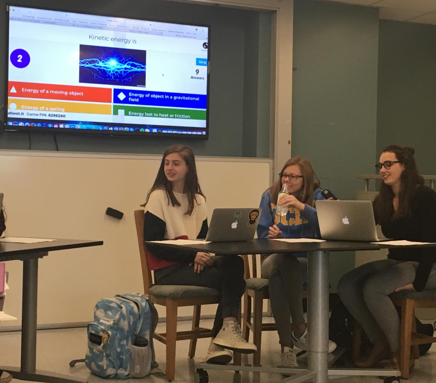Juniors Emma Kob, Molly Brown, and Amelia Estes participate in a Kahoot quiz before their physics class. The Kahoot reviewed topics they had gone over earlier in the semester as a refresher.