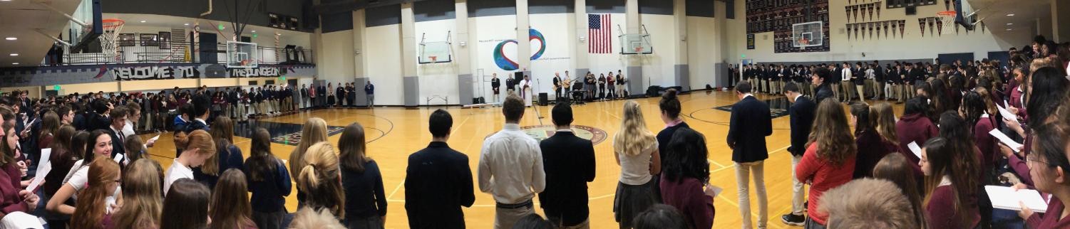 Students and faculty stand in the Stuart Hall gym as teacher Paul Pryor-Lorentz speaks to the audience to begin the Ash Wednesday service. The ceremony was held before first period and consisted of individuals from Convent and Stuart Hall High School.