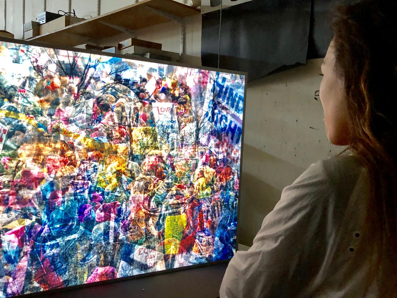 Day El-Wattar views one of Jim Campbell's pieces made from photos at the 2017 Washington D.C. Women's March. The work is made up fluorescent lights shining through a layer of 12 different photos from the event.