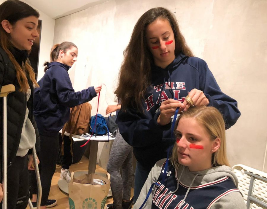 Sophomore Isabelle Thiara braids junior Grace Boudreau's hair adding red and blue ribbon, the team's colors. The Syufy Theatre was filled with the Knight's colors and spirit before the game, as almost all students have some sort of accent in their hair, on their face or around their body.