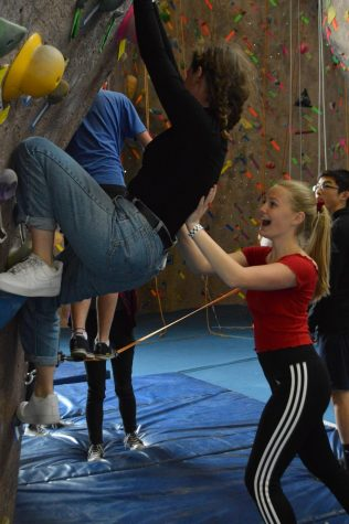 Junior Abby Anderson supports junior Poppy Cohen at a bouldering wall during this year's annual Congé. School buses transported students to Bladium Sports Center in Alameda, CA for a variety of activities.
