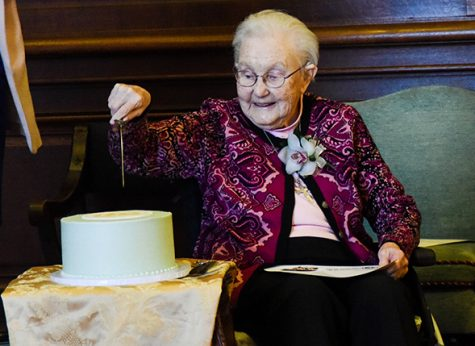 r. Mary Mardel cuts into the cake for her 100th birthday celebration in the Mary Mardel, RSCJ Chapel. The cake was covered in mint green frosting and featured the original Society of the Sacred Heart seal in yellow on top.