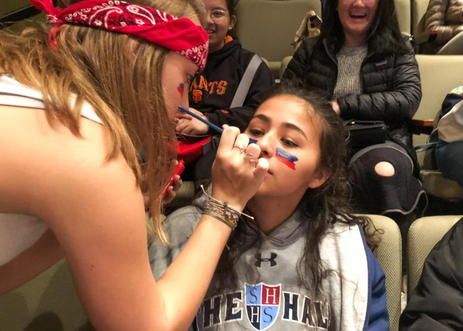 Sophomore Jacqui Carlson paints the Knight's colors on junior Izzy Gutierrez's face. Many students brought face paint in white, red, blue and silver to support the team.