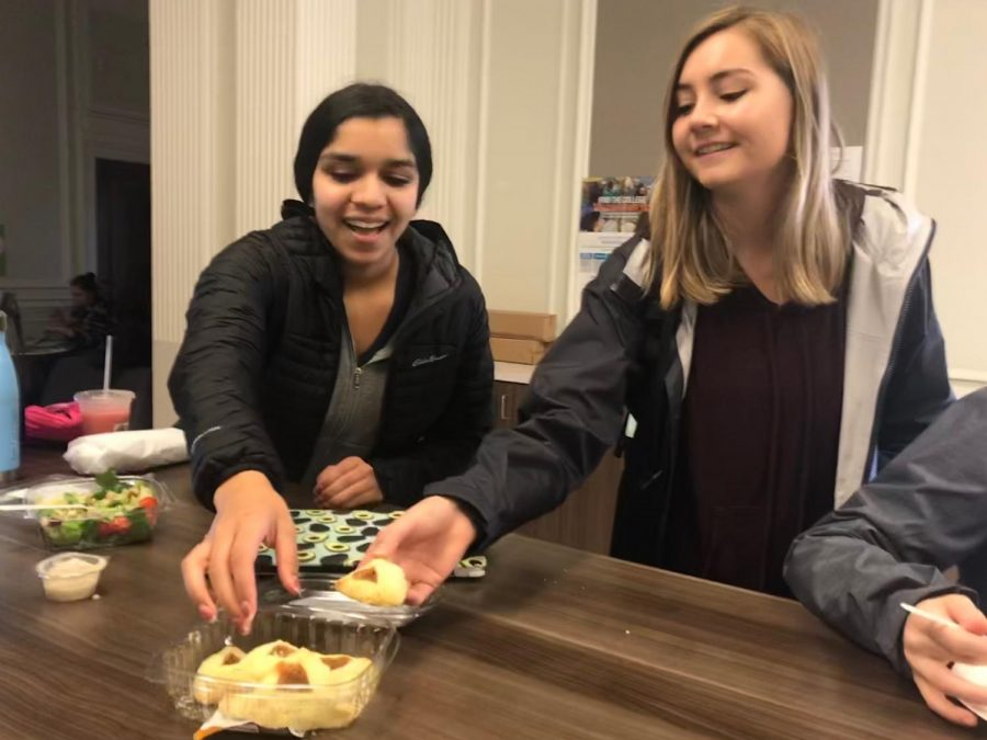 Sophomores+Avani+Mankani++and+Brooke+Wilson+eat+hamentashens+in+the+center+during+lunch+to+celebrate+the+Jewish+holiday+Purim.+Hamentashens+are+traditional+triangle+shaped+cookies+eaten+primarily+during+Purim.