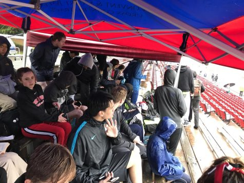 Athletes sit under the team tent to protect themselves from the rain while watching the races. The rain stopped in the late afternoon.