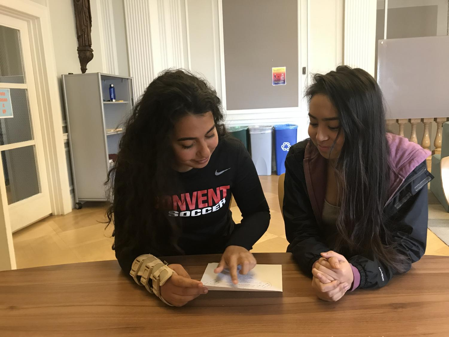 Sophomores Nisrine Rahmoui and Rachel Santamaria look over a poem written by Rahmoui. The annual poetry contest will on Monday April 30th.