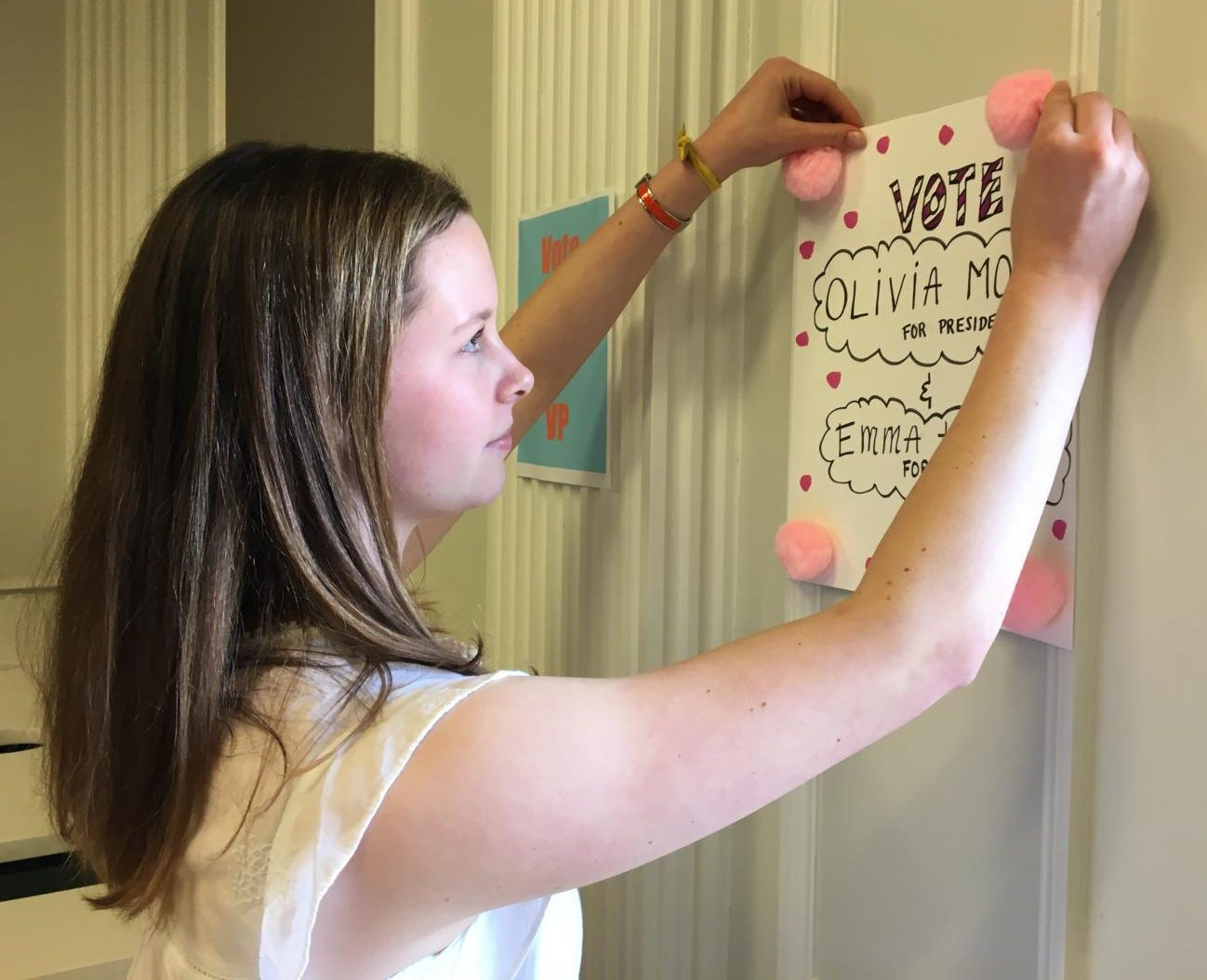 Junior Emma Hubbard hangs a campaign poster in the Center for her and junior Olivia Mohun, who are running as a President and Vice President team. Elections will be held in the Chapel on Monday, and results will be posted by the end of the day.