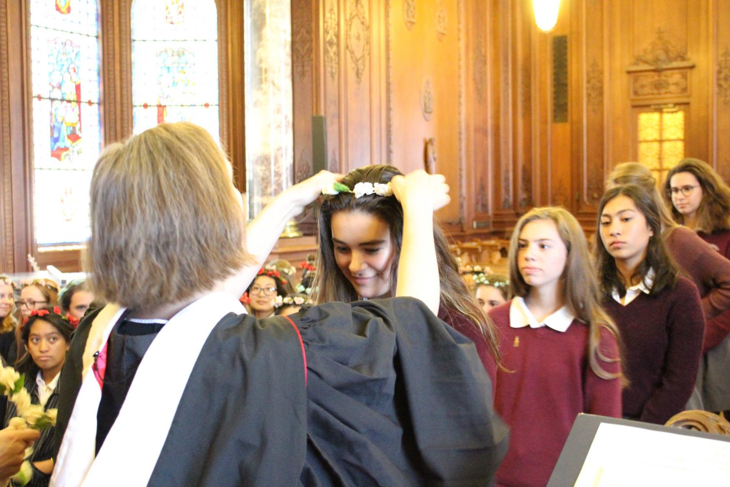 Head of School Rachel Simpson places a floral wreath on the head of sophomore Kate Hindley during the 131st annual Prize Day ceremony. Each student received an award signifying the completion of their academic year.