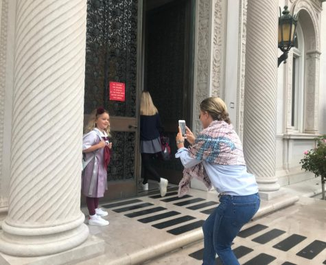 Mother takes a photo of her daughter on the first day of school. Grades K to 12 began school today at 8 am.