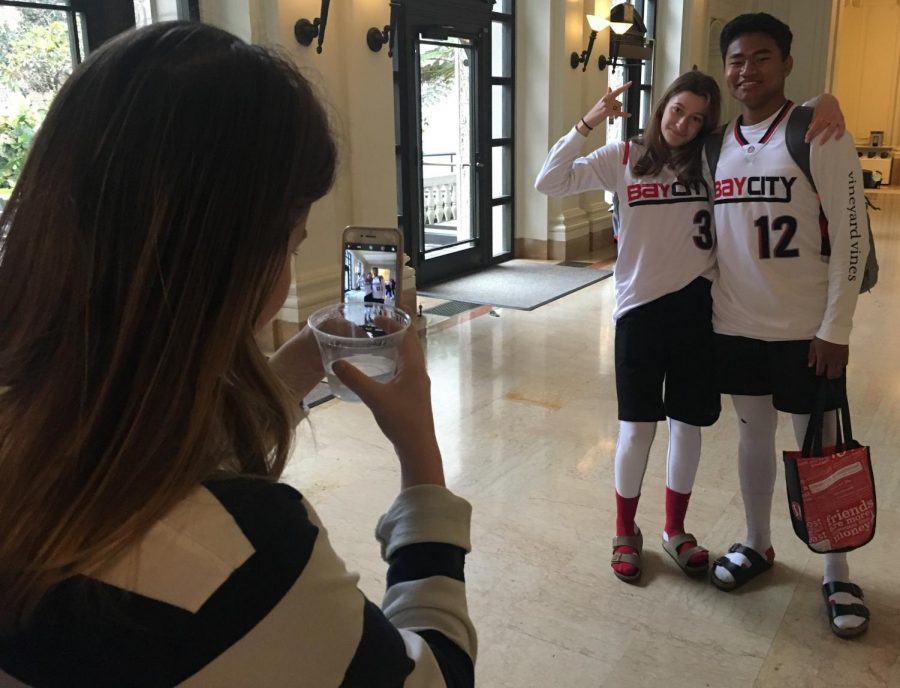 Senior Olivia Mohun takes a picture of senior Kiki Apple and junior Cole Slater in their matching outfits before schools starts. Students 'twinned' with friends, teachers or in a larger group.