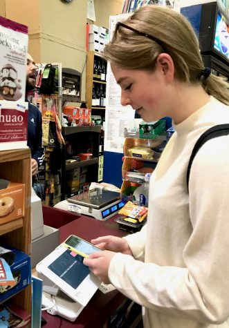 Senior Anna Doggett pays for her lunch at Mayflower Market using Apple Pay, like she does most days. Instead of cash, Doggett uses mobile payment methods more often than she uses cash or a debit card when purchasing her meals or buying products.