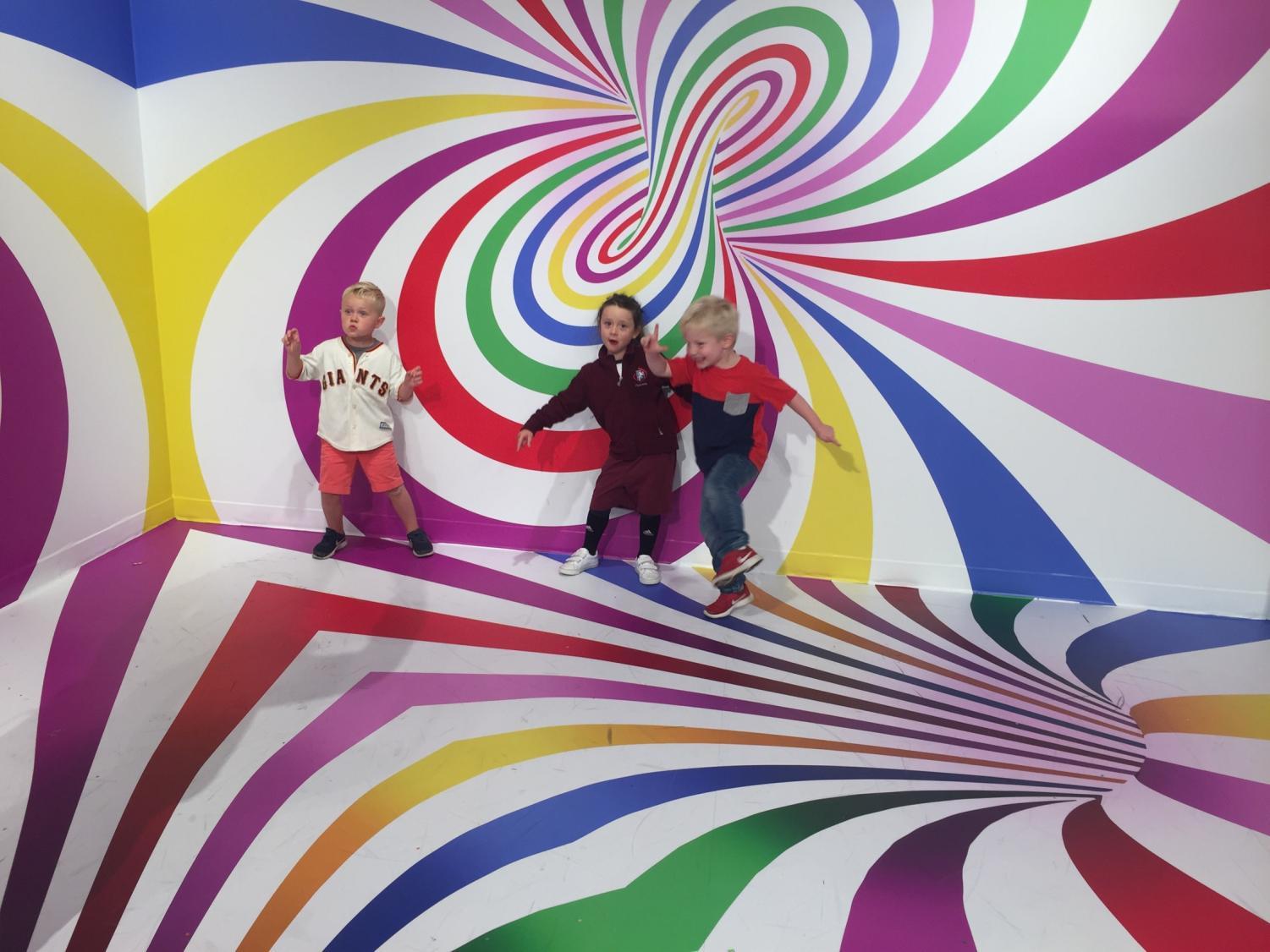 Faculty children Sebastian Galringhouse and Isla Abbott play with their friend Elliot Stewart-Kahn in one of Candytopia's installations. The museum opened on Sept. 6 and aims to be an engaging place for all ages.