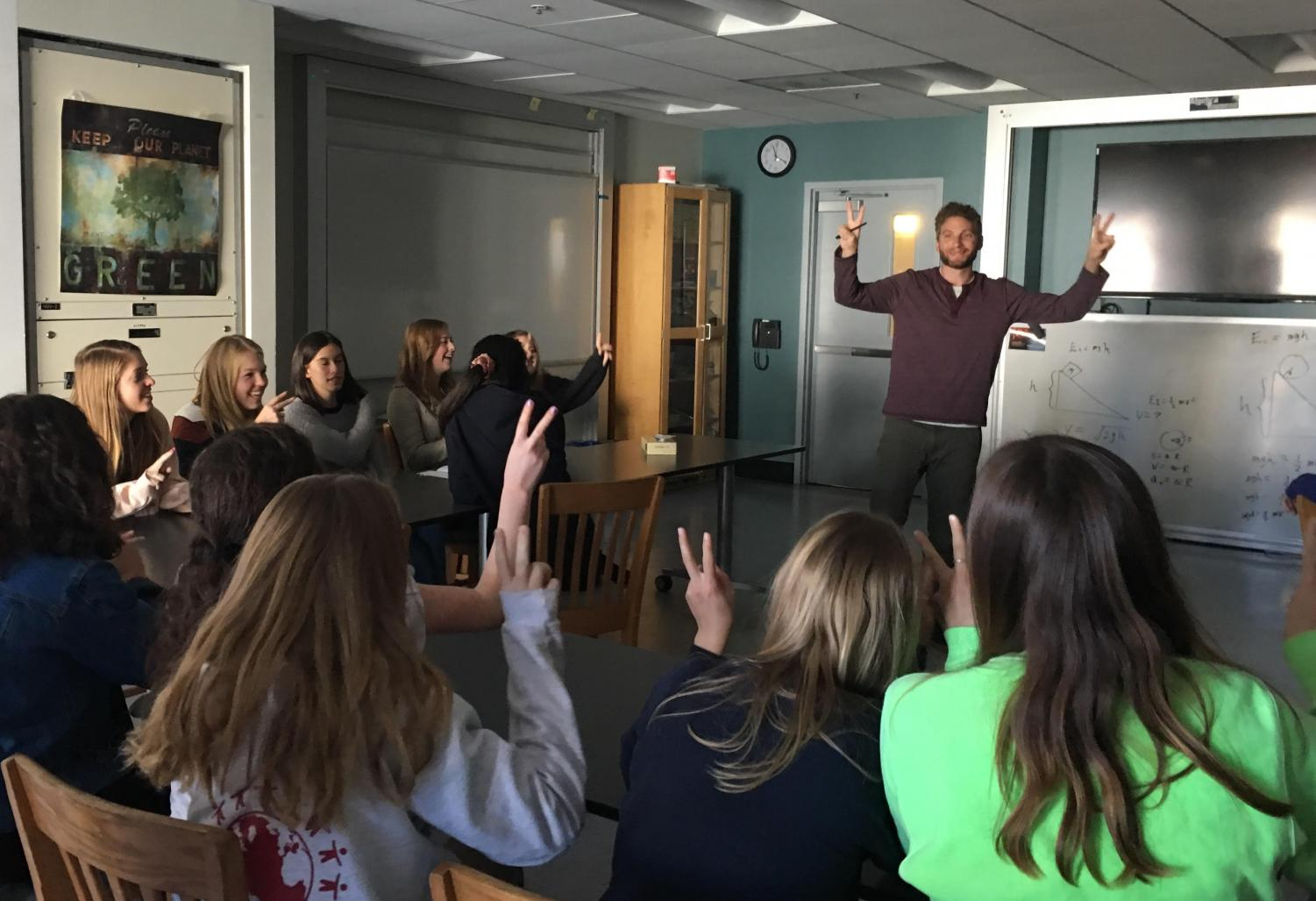Spanish students sing with hand motions during the Noёls rehearsal with Spanish teacher Anthony Reyes. The peace signs represent the line