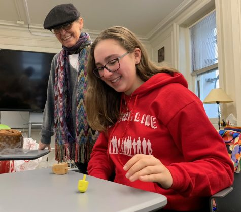 Sophomore Lili Levy plays with a dreidel during the Interfaith club's Hanukkah celebration. In addition to Hanukkah, the club has honored other religious traditions and holidays.