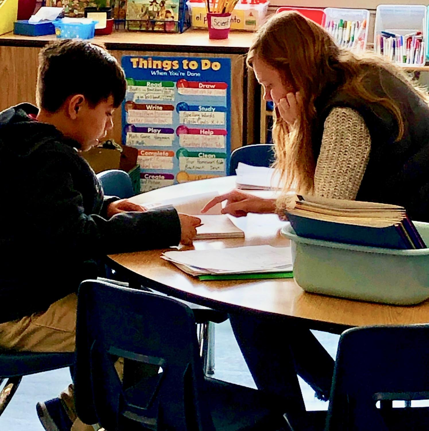Senior Molly Brown tutors a student at the Spring Valley Science Academy during her B Period Social Awareness & Action class. Students volunteered at organizations of their choosing and completed written reflections on their experience for the class.