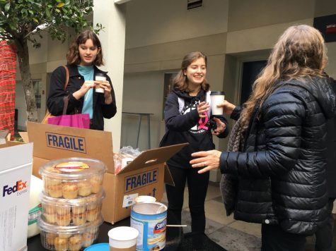 Laurie Pomeranz, the teacher advisor of Knight Light, hands junior Sofia Telfer a hot chocolate before A Period finals. The Knight Light club provided beverages and snacks for students on the Pine-Octavia campus to ease stress before finals.
