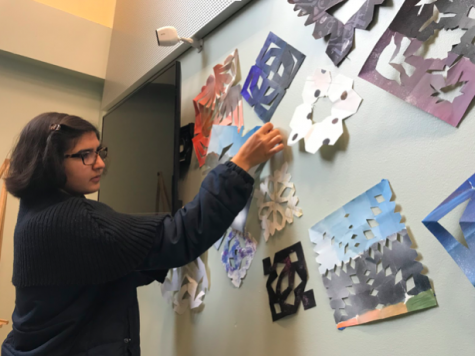Junior Arianna Nassiri tapes snowflakes on the wall outside of the Syufy Theater for the art show. The exhibit will open on Dec. 12.