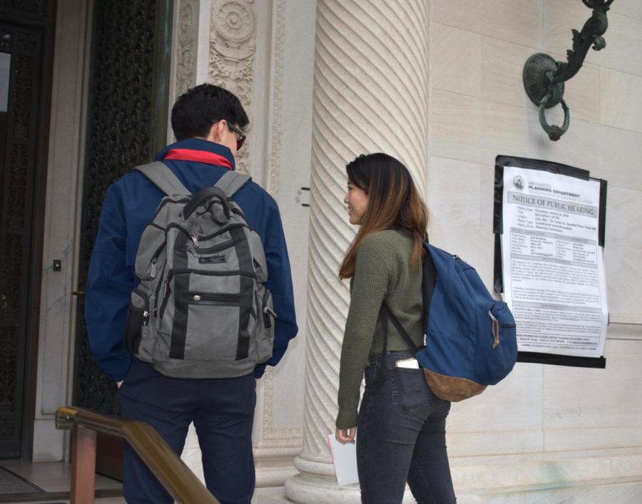 Sophomores Nina Sanchez and David Louie-Grover walk into the Flood Mansion, passing a notice of the upcoming public hearing on the school's application to increase student enrollment. The hearing was originally scheduled for Jan. 24 but has been postponed until April.