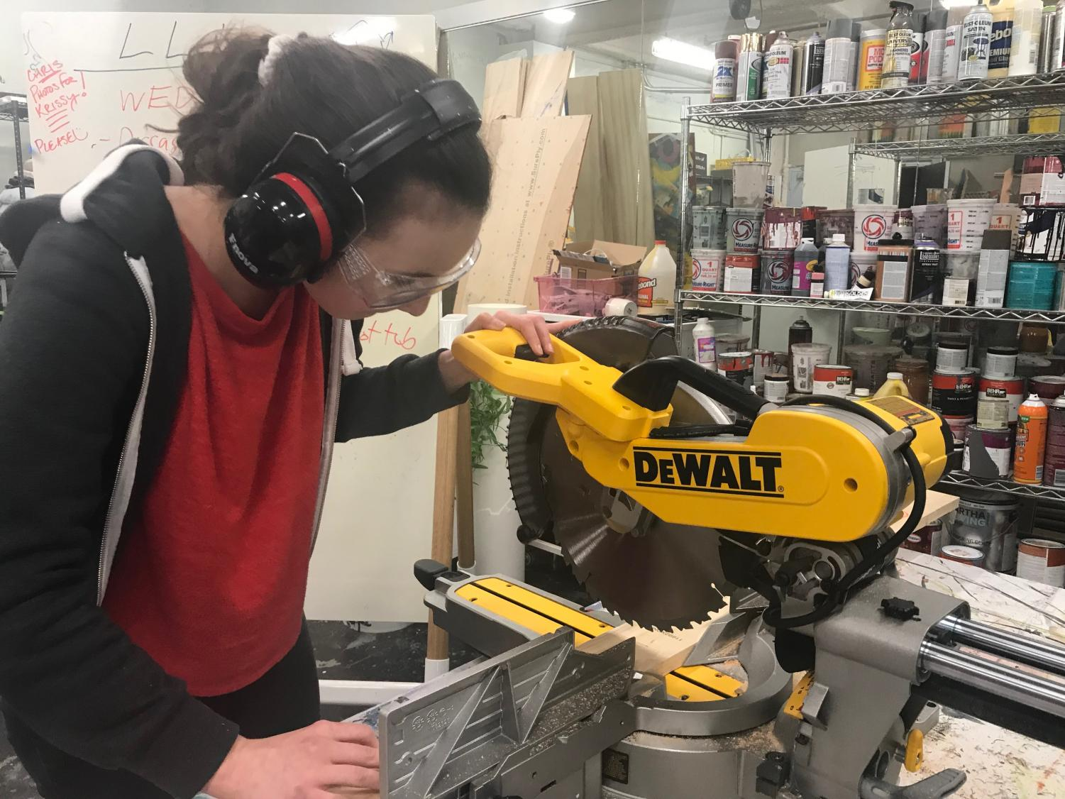 Freshman Alia Mogannam uses a saw to construct a piece of the set. The crew spends about 10 hours a week working on the show.