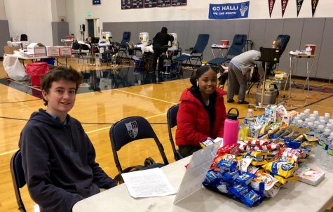 Junior Jade Despanie and Senior Elias Garvey help set up the blood drive. The event was held in the Stuart Hall gym.
