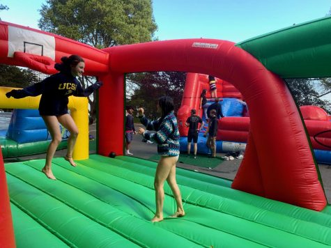 Juniors Lila Horwitz and Kai Johnson bounce on one of the bouncy houses at Paradise Beach County Park during Congé. There was also a beach and grass fields for playing sports or relaxing.