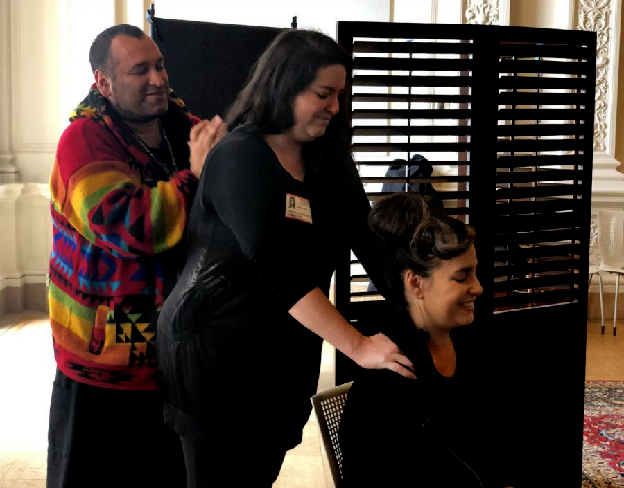 Masseuse Carlos Hu demonstrates on Nicole Holt how to apply pressure to the shoulders in order to relieve tension. Hu, Holt, and Nina Stavinga were at the end of their shift, having given chair massages to faculty and staff throughout the day.
