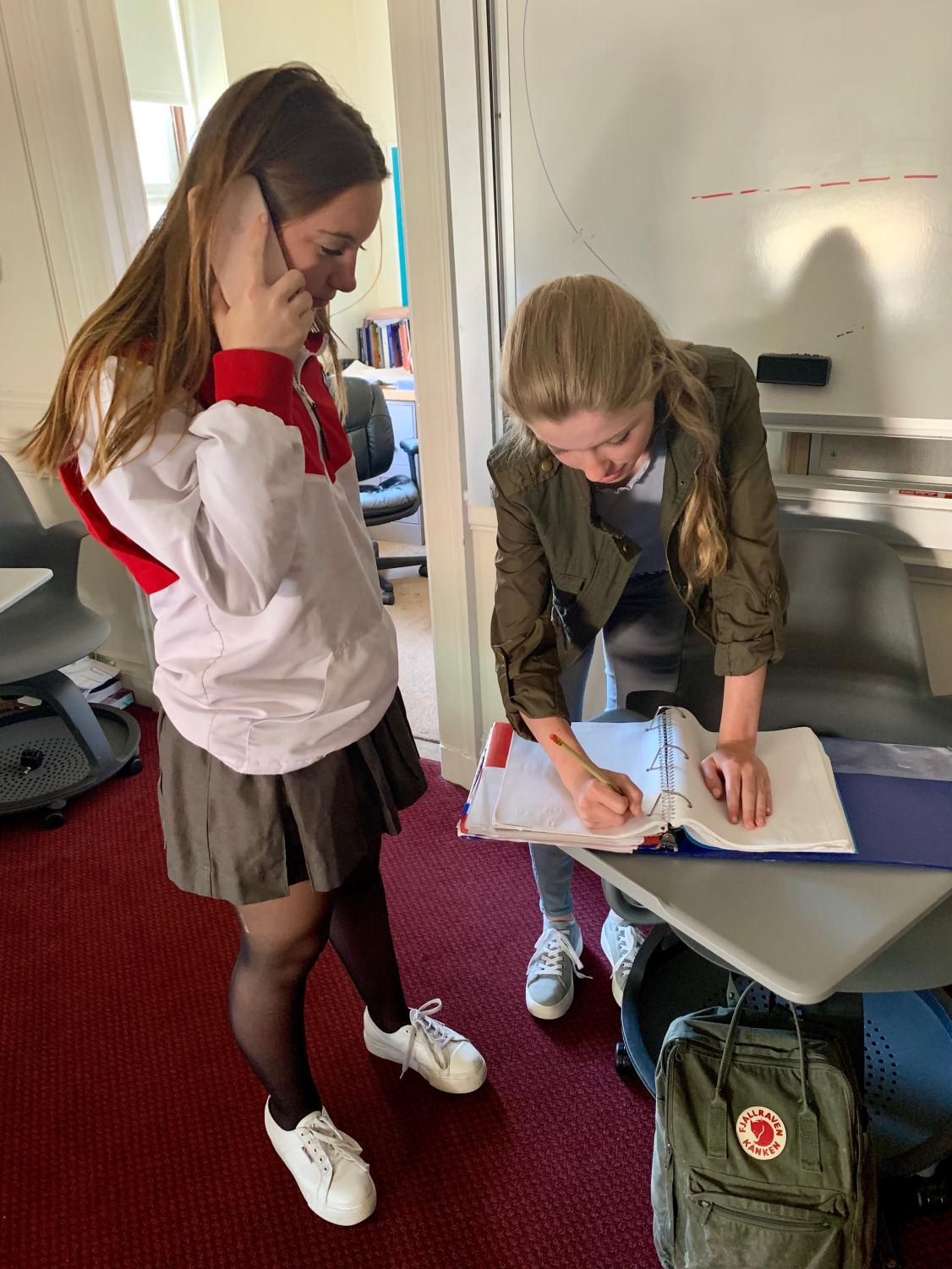 Sophomores Naia Urruty and Olivia Callander take notes while interviewing Jules His, a former exchange student from a Sacred Heart school in Nantes, France. Students were encouraged to speak to foreign exchange students to gain more  personal information about their exchange experiences.
