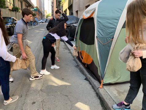 Freshman Shelby Low hands out a lunch to someone living on the streets of the Pol Gulch district in San Francisco. The freshman class made and passed out lunches for their Freshmen Signature Service Project.