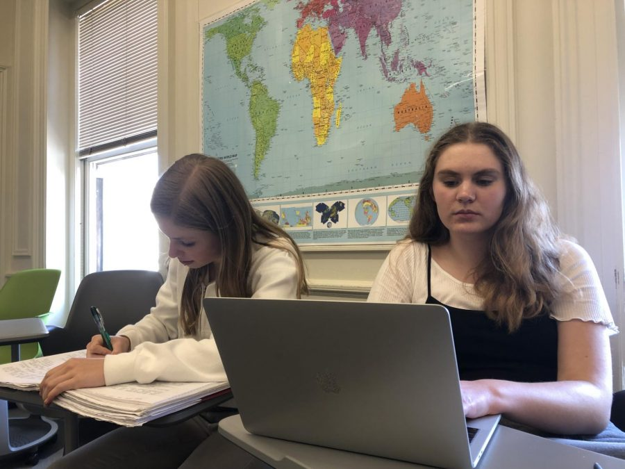 Sophomores Olivia Callander and Amy Phipps take notes during a final lecture on World War II. Students will have the opportunity to use these notes during an in-class writing assignment later this week.