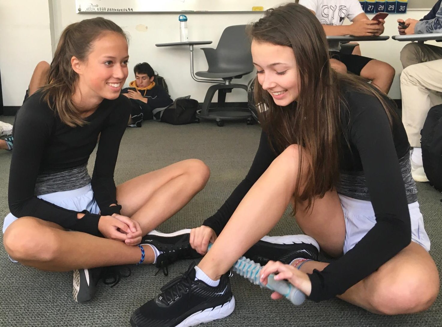Freshman Amelia Abernethy and Madeline Thiara stretch and use the muscle roller stick before practice on Tuesday. Yesterday runners had twin day to celebrate track and field's spirit week.