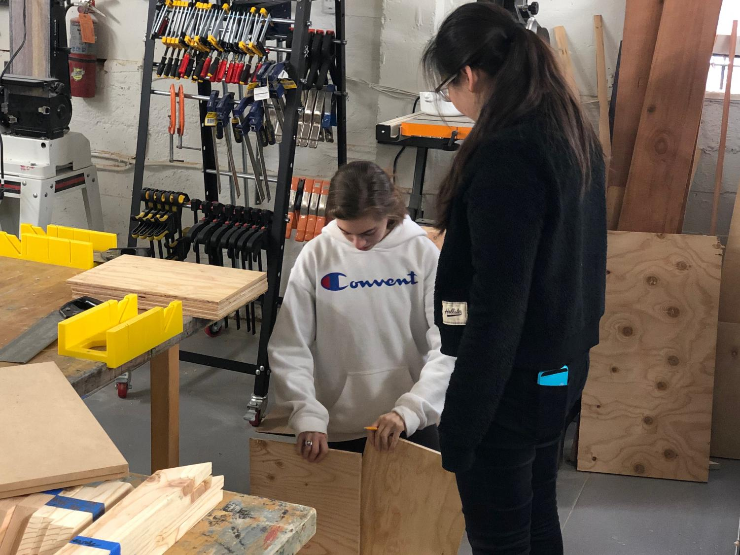 Junior Zoe Hinks and Michelle Wang measure the dimensions of a dollhouse they are creating for their International Baccalaureate Creativity, Activity and Service Project. They have been working on the project since February in the Herbst House wood shop.