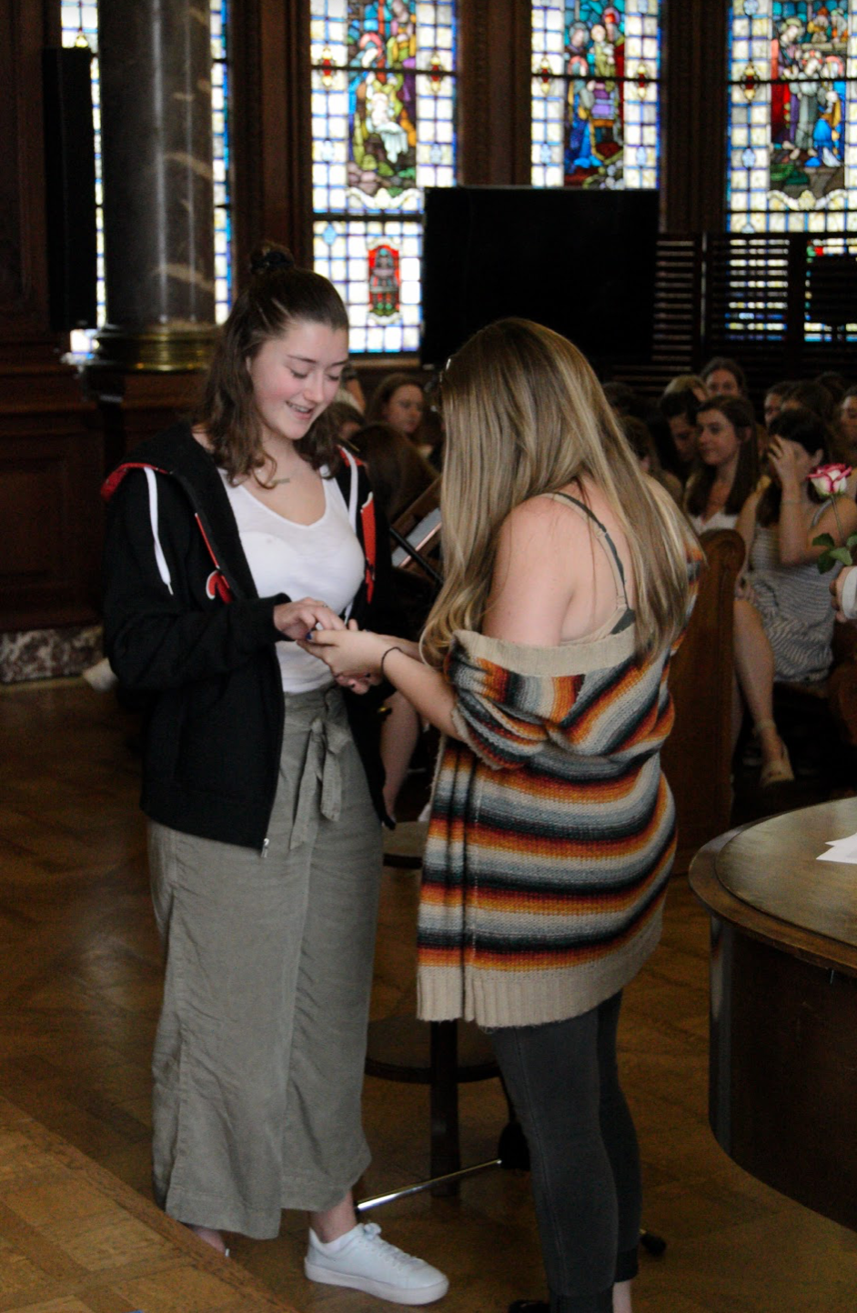 Graduating senior Delaney Tobin presents junior Margaret Millar with her class ring. The Ring Ceremony is a Sacred Heart tradition.