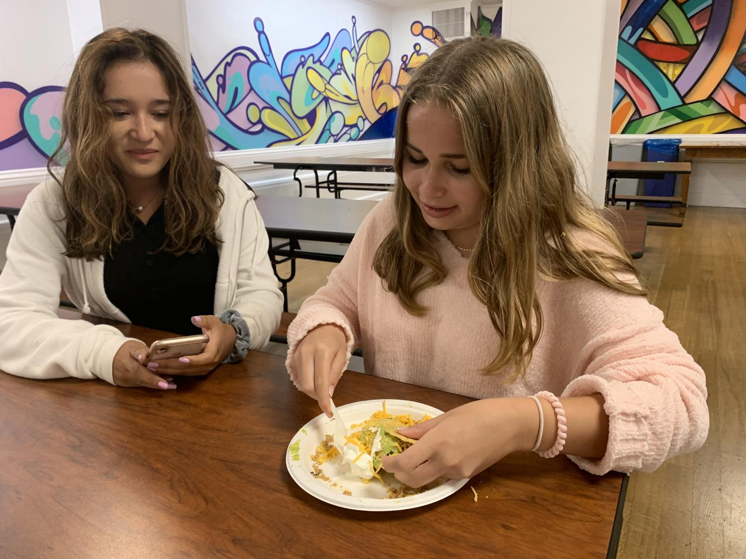 Sophomores Sloane Riley and Mira Chawla eat lunch during the second lunch period at Convent. The modified lunch schedule allows for two lunch periods based on the location of a student's first afternoon class.