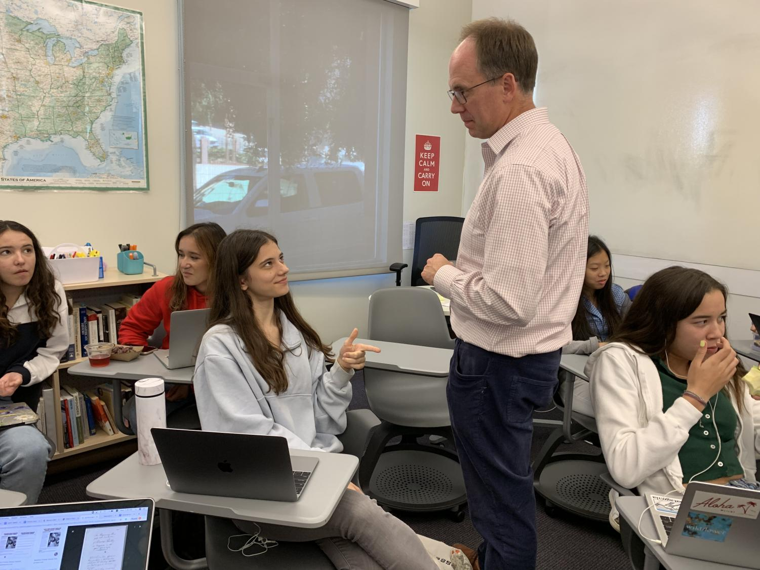 Sophomore Lily Peta asks history teacher Michael. Stafford a question about the early colonists. The class consisted of both discussion and writing time.