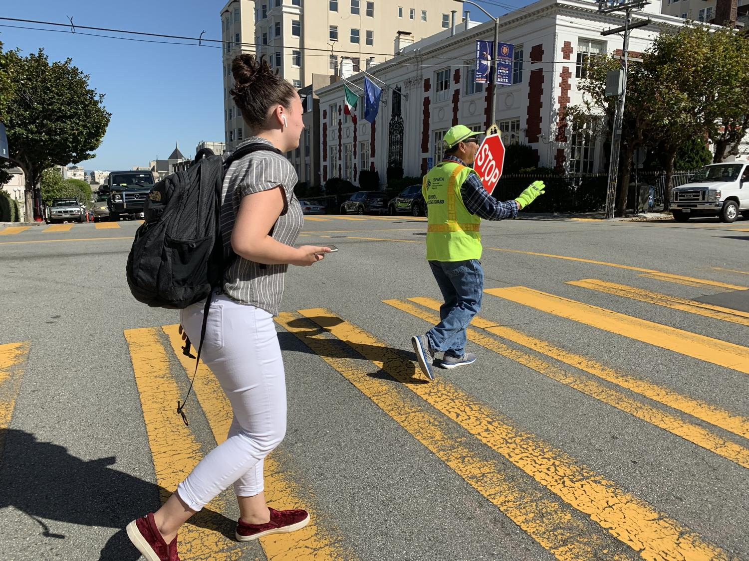 Senior Dena Silver crosses the intersection of Broadway and Webster streets with the help of a crossing guard. Traffic commissioners work during drop-off and pick-up to ensure safety.