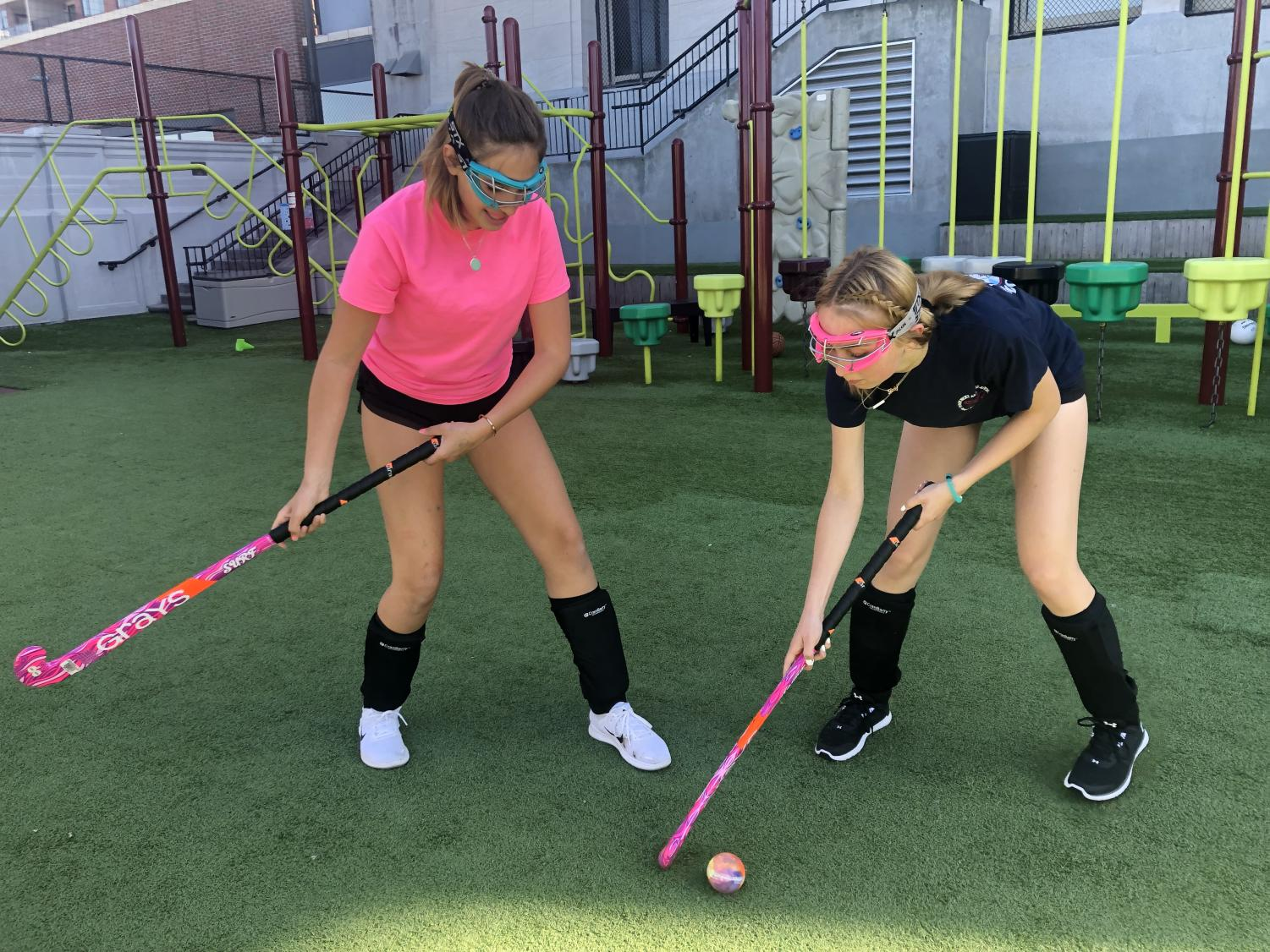 Sophomores Finley Simon and Takohui Asdorian dribble at practice on Syufy Court. Field hockey practices four times a week.