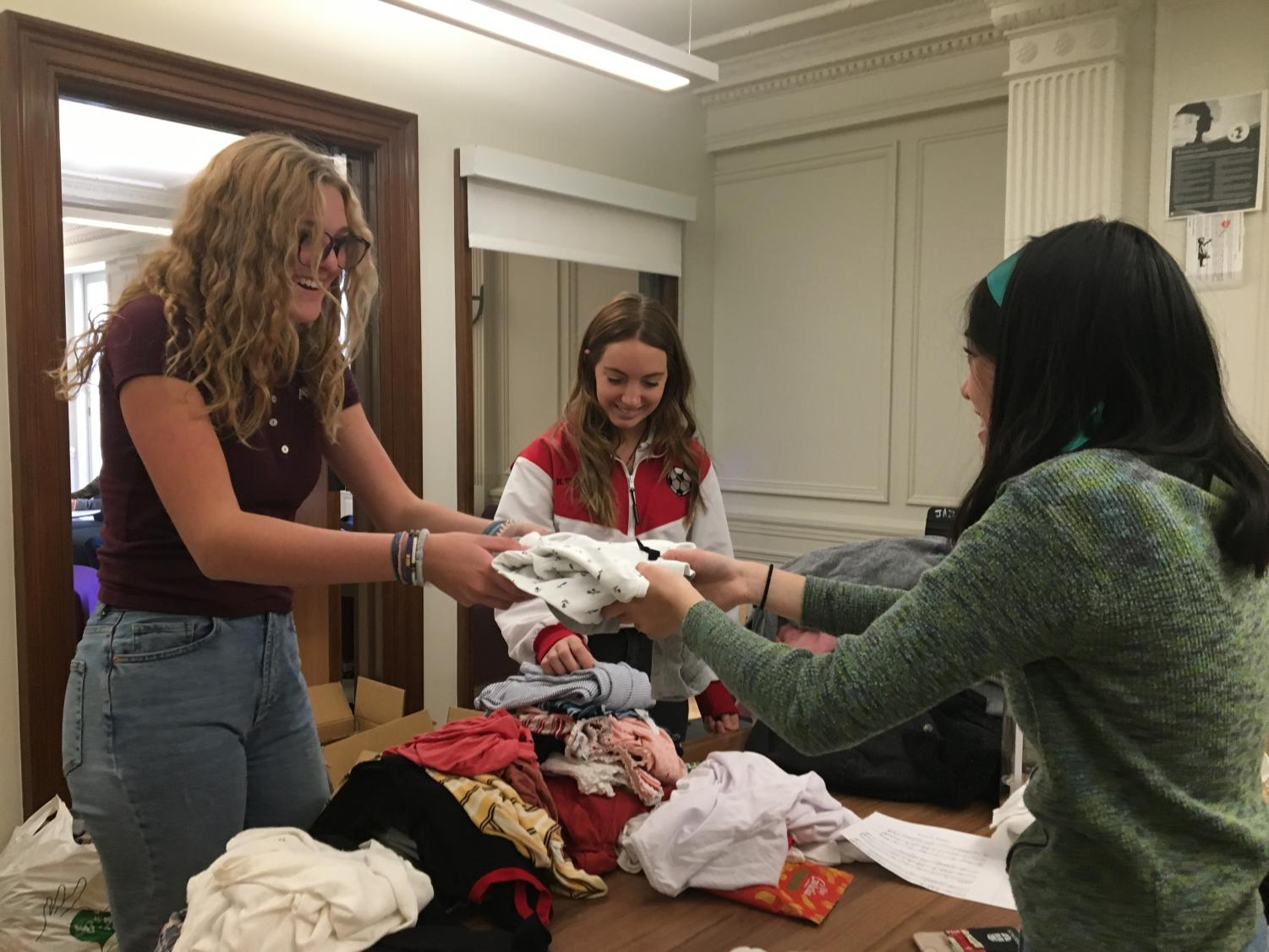 Sophomore Anneli Dolan donates a shirt to the Eco Friends clothing swap.  Thrifting and purchasing second-hand helps to reduce plastic in landfills and carbon dioxide emissions.