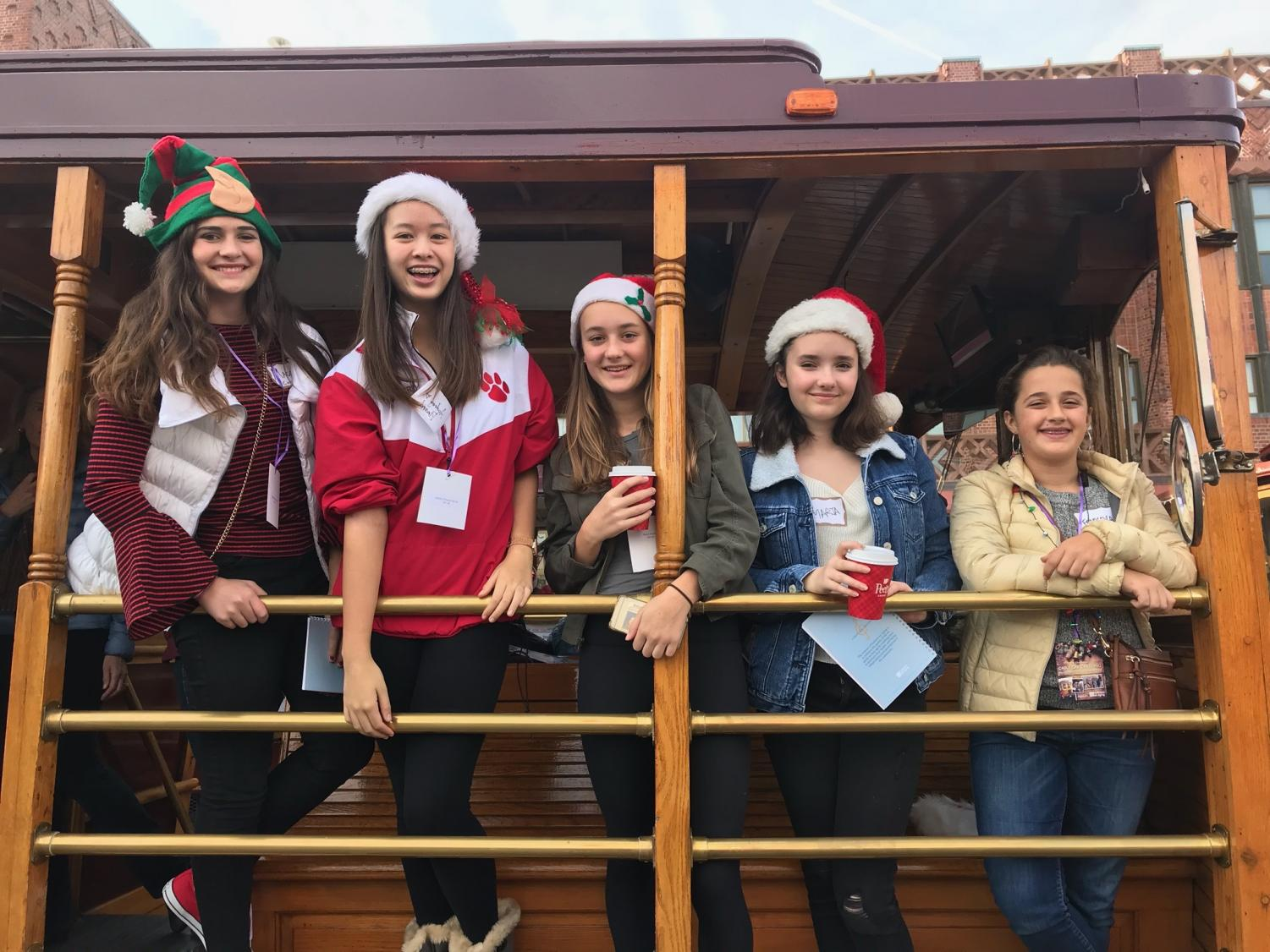 """Junior Audrey Pinard smiles with her friends at the National Charity League with the Institute of Aging's """"Cable Car Caroling."""" This year's caroling was canceled due to rain."""