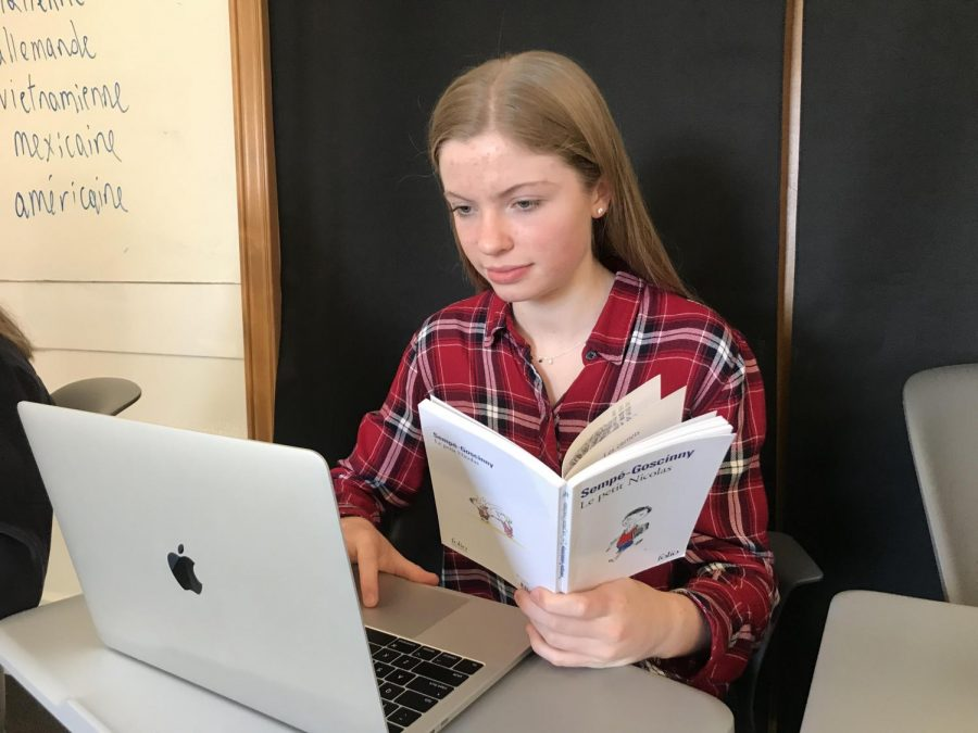 Junior Olivia Callander works on her play based on the French children's book Le Petit Nicolas. Students created a script based a chapter in the book and they will be acting them out.