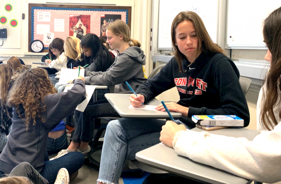 Sophomore Madeline Thiara writes a reflection about personal and community values. Students were organized into small groups to share what they wrote.