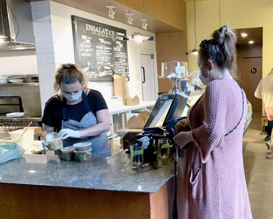 A customer picks up a take out order from Insalata