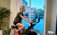 Sophomore Ella Runneboom rides her Peloton in the guest room in her home. She participated in a 20 minute workout led by instructor Ally Love, the ride featured 90's music.