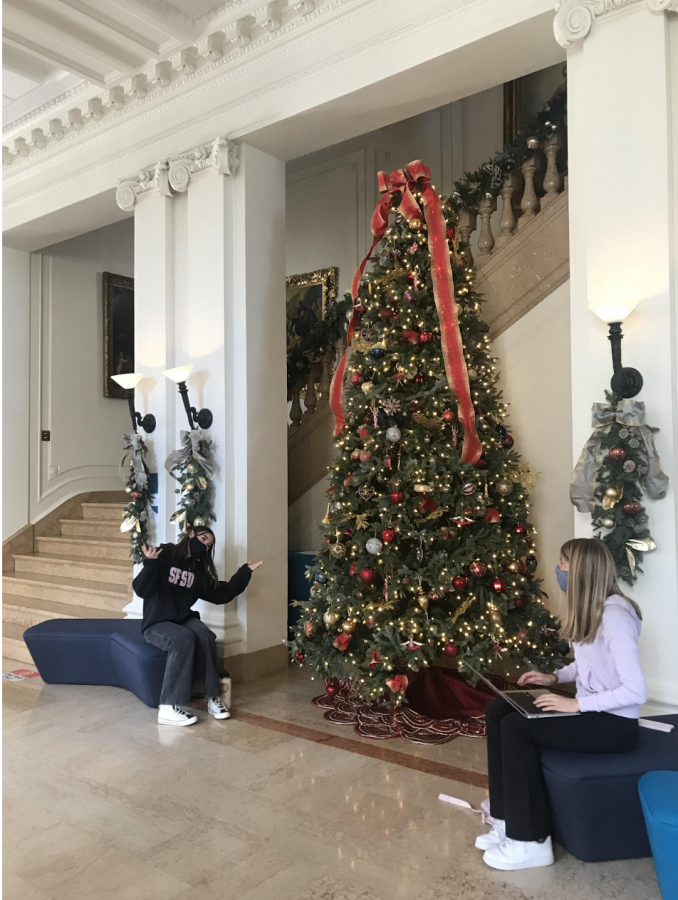 Juniors Devon Carlson and Bridget Mills admire Christmas decorations in the Main Hall. Two Christmas trees sit in the Main Hall while wreaths and garlands line the stairwell and walls.