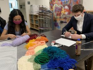 Seniors Alliza Manayan and Wolfgang Tobaison work on large-scale art pieces in preparation for the art show opening March 11. Seniors have worked on their exhibition as a part of the IB Visual Arts course.