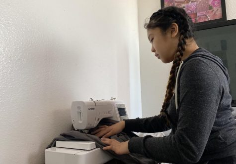 Sophomore Isabella Alarcon, who runs a business reselling her customized clothing, alters a sweatshirt. A 2018 study of 1,000 teens showed that 41% would consider entrepreneurship as a career option versus working in a traditional job, according to Junior Achievement.