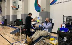Stuart Hall Head of School Tony Farrell examines his arm after giving blood at the Sept. 2 Vitalant blood drive. The Whole blood donations process takes roughly 1 hour, according to the American Red Cross.