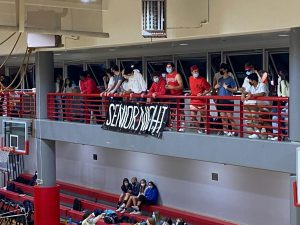 Student fans support the varsity volleyball players and watch from behind the student-made banner. Many family and faculty members came to watch the game to support the seniors.